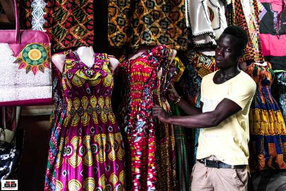 Kwame Boateng fitting a mannequin in his shop.